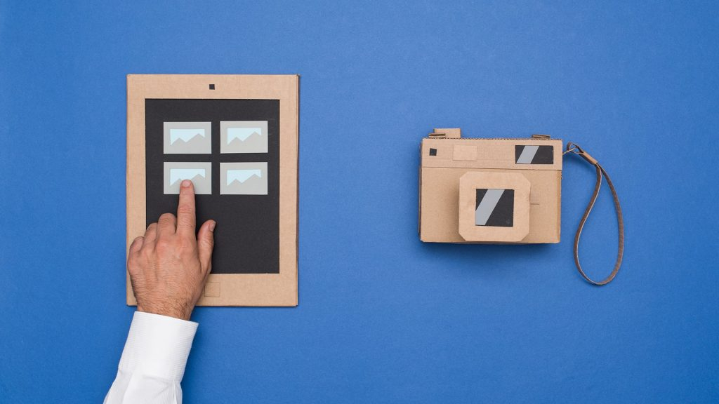 A cardboard cut out of a camera and  a man arranging images on a device.