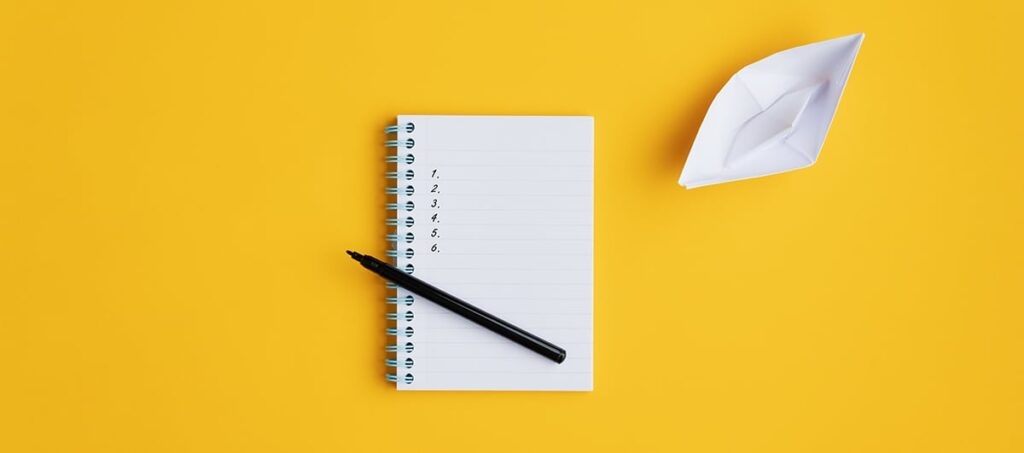 A note pad with a list written on it and pen.